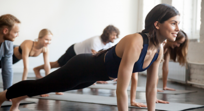 woman strengthening her core with practicing plank pose, at group yoga class.