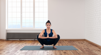 Woman practicing yoga for flat feet Garland Pose (Malasana)