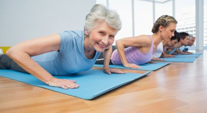 An older woman in a yoga class in Cobra Pose (Bhujangasana) practicing yoga for osteoporosis