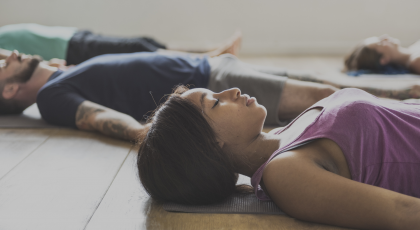 Yoga class practicing for stress relief in Corpse Pose (Savasana)