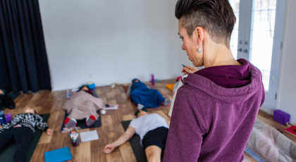 yoga instructor guides trauma-informed yoga class
