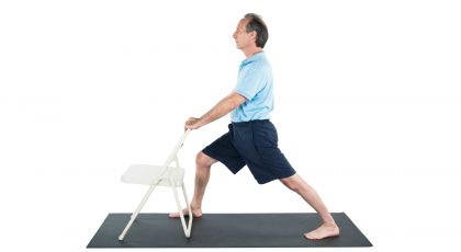 older man practicing yoga warrior 1, virabhadrasana I, yoga pose variation with chair