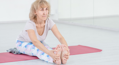 Older female yoga student practicing paschimottansana seated forward bend pose