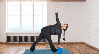 Woman practicing yoga Revolved Triangle Pose (Parivrtta Trikonasana)