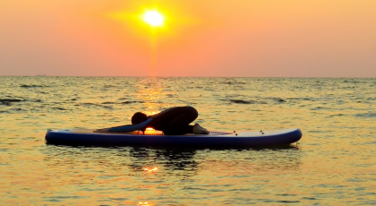 A yoga practitioner practicing Child's Pose (Balasana) on a kayak to benefit of self-awareness