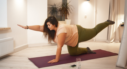 Woman practicing core strengthening yoga Balancing Tabletop Pose