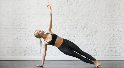 Woman practicing yoga, vasisthasana, side plank pose, for scoliosis benefits