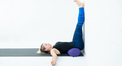 yoga woman practicing legs up the wall pose with bolster modification