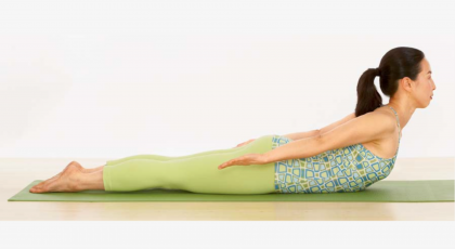Woman practicing yoga salabhasana locust pose.