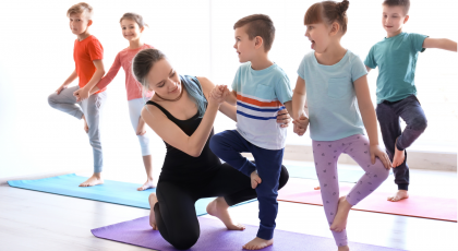 Yoga class for kids in school practicing Tree Pose (Vrkasana)