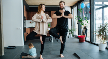 Family practicing yoga in Tree Pose (Vrksasana)