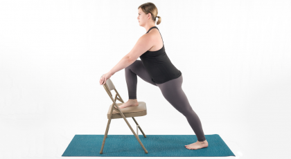 Woman practicing yoga, warrior I with chair