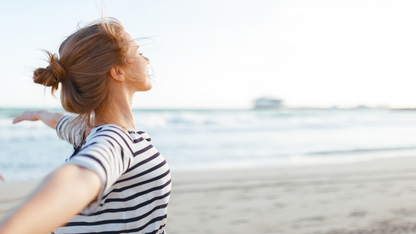 happy young woman enjoying freedom with open hands on sea