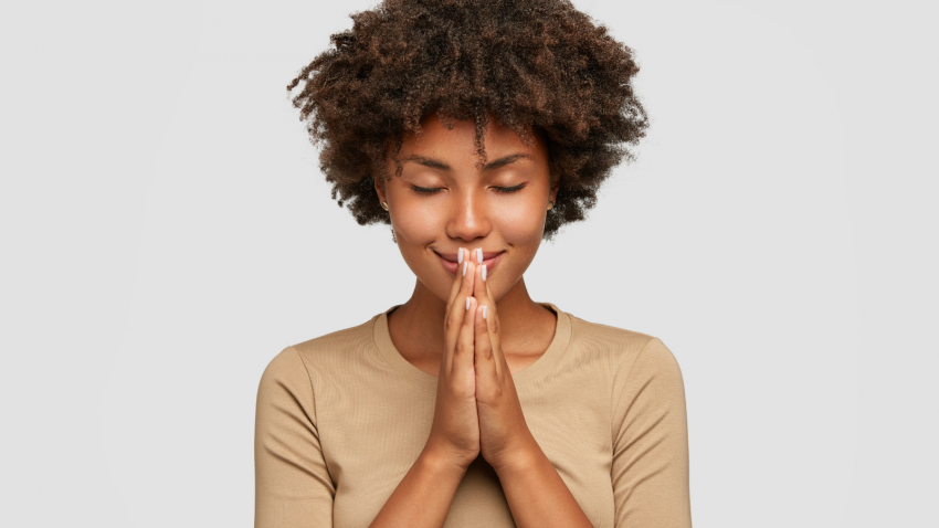 Beautiful young black woman stands in meditative pose, holds hands in Anjali Mudra