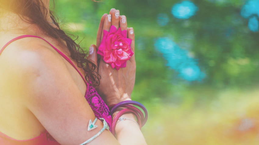 Close up of yoga woman hands in namaste gesture with rose flower outdoor summer day light leak
