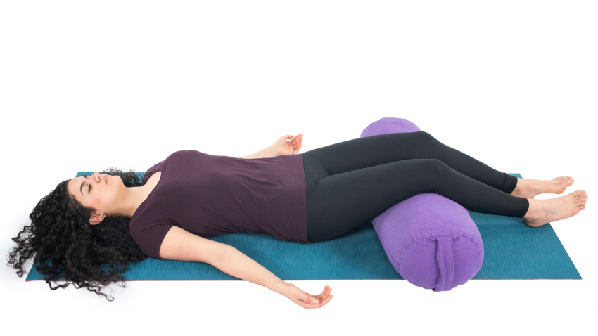 Savasana or Corpse Pose with a bolster for extra comfort for the knees