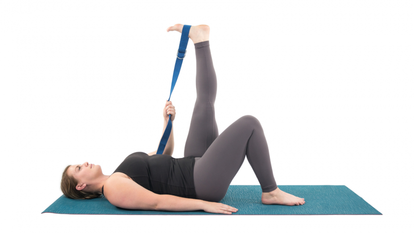 Yoga student practicing the supine pose Supta Hasta Padangusthasana with the help of a yoga strap