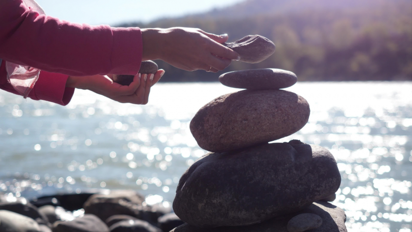 pebble stack next to the mountain river symbolic of slowing down and enjoying the awe of nature