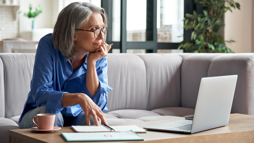 older woman taking online webinar on laptop remote working or social distance learning from home