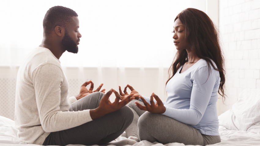 Pregnant woman doing yoga with her husband at home, sitting on bed face to face with closed eyes