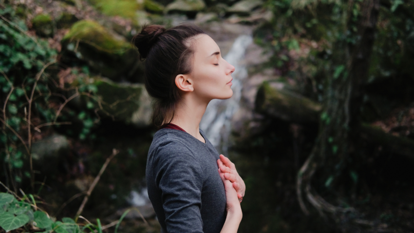 woman near a waterfall, practicing breathing and yogic affirmation of going with the flow of Life