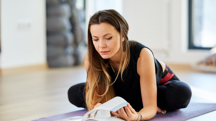 Woman studying yoga from a book on her yoga mat