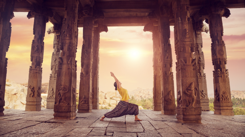 Woman Practicing Warrior 1 in a temple
