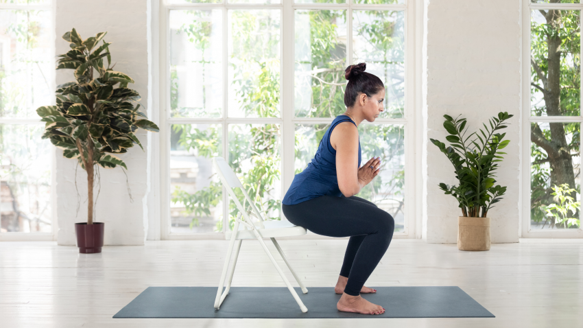 Woman practicing Chair Pose Utkatasana on a folding chair.