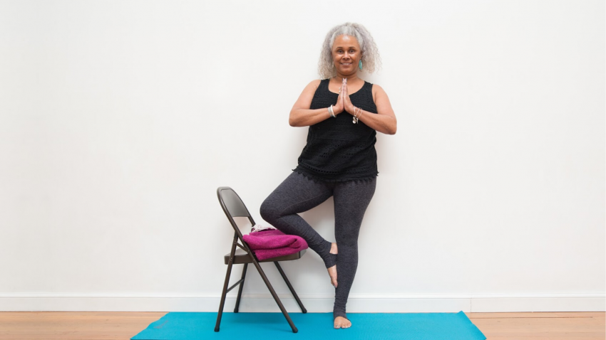 Woman practicing tree pose with a chair for support.