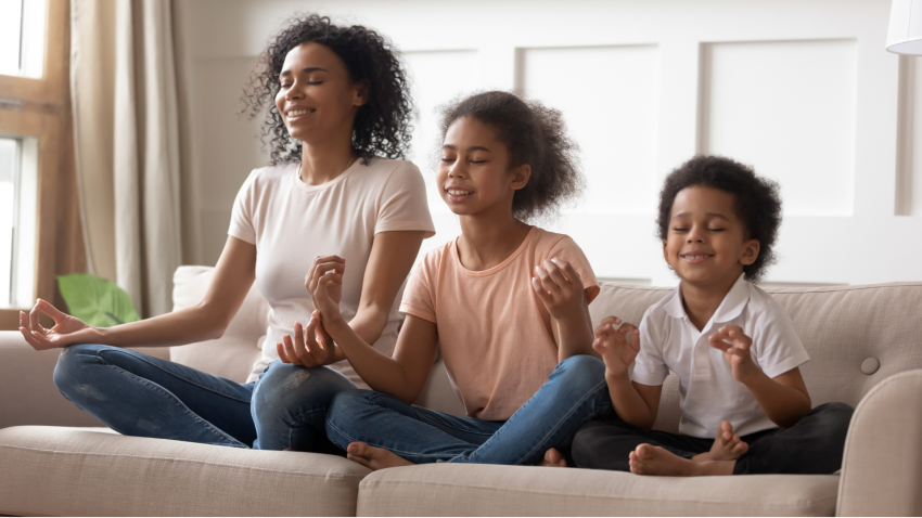 Mother and children practicing yoga in Seated Pose