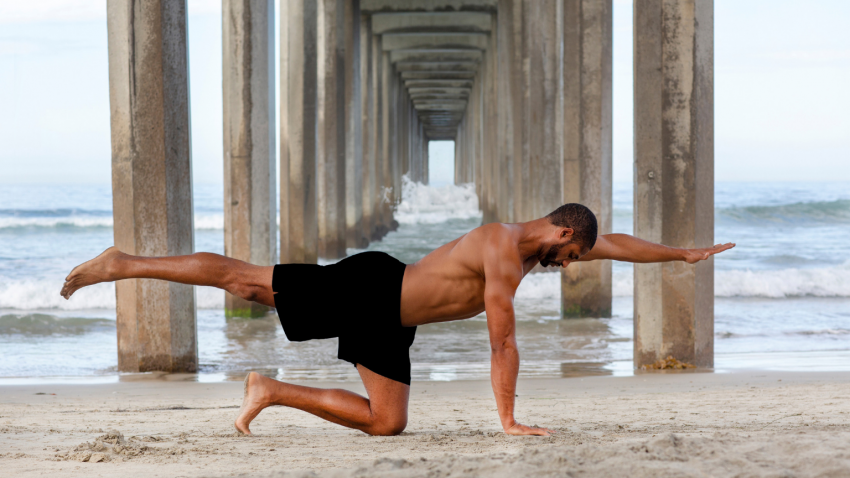 man practicing yoga, bird-dog pose on the beach
