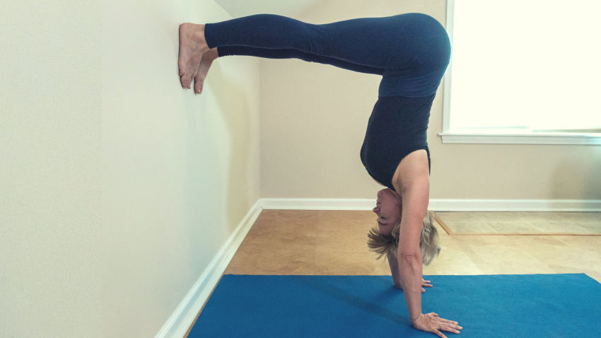 Woman practicing L Handstand Yoga Pose after doing prep sequence