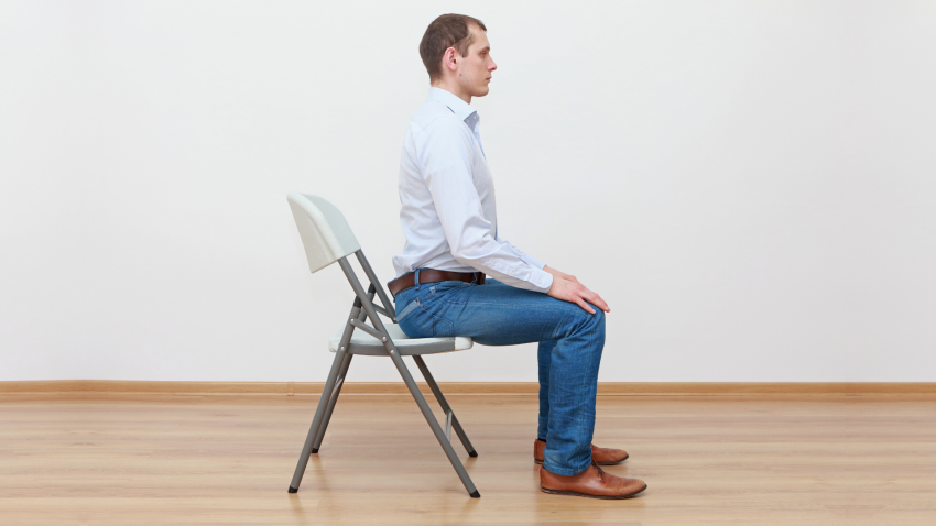 Man practicing yoga pose in a chair