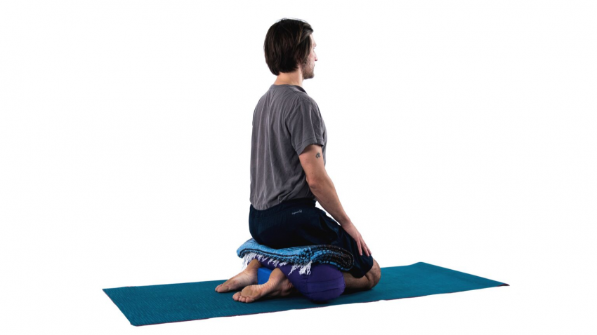 man practicing yoga virasana with roll modification