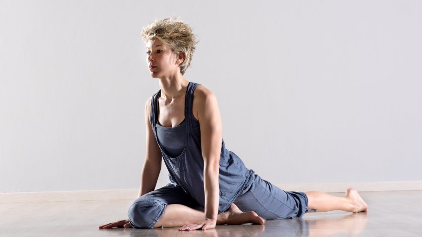 A woman in Pigeon Pose (Kapotasana), practicing yoga for osteoporosis
