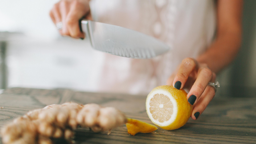 Yoga teacher cutting lemon and ginger to improve her digestion