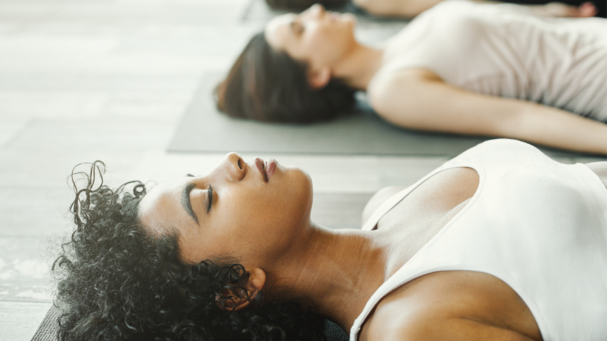 Women practicing yoga savasana