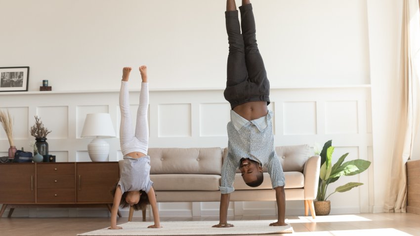 A man and his child practicing yoga Handstand Pose