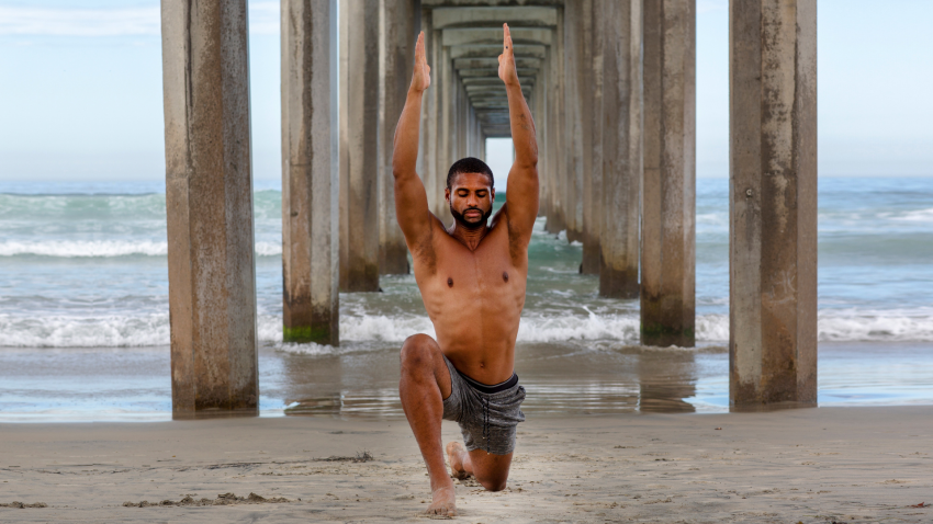 Male Yoga Instructor relaxing in Low Lunge Pose with Arms Overhead, on beach
