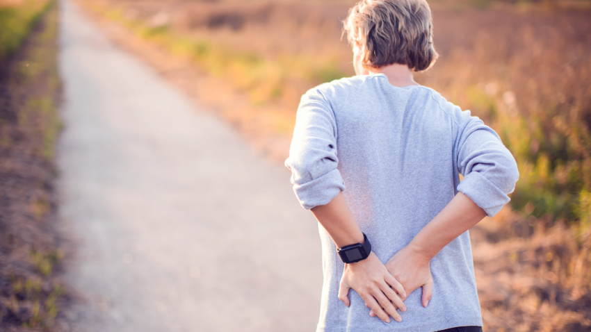 Image of older woman experience back pain on a walk