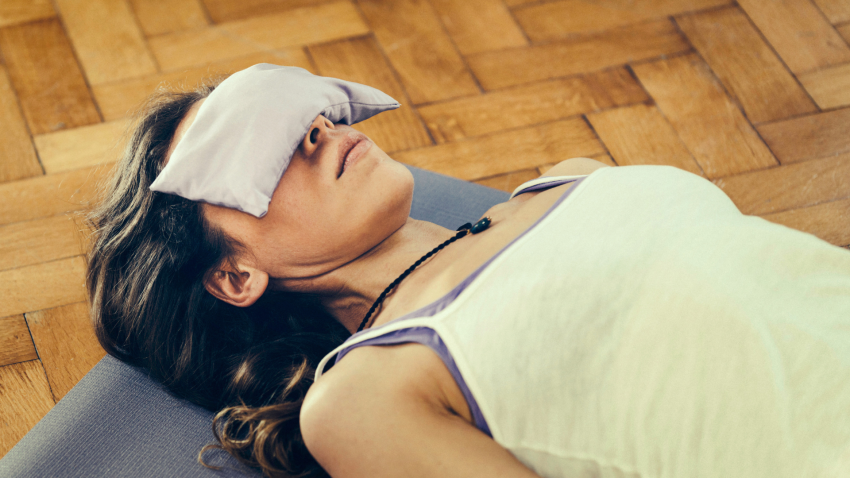 woman practicing yoga savasana with eye pillow to aid sleep