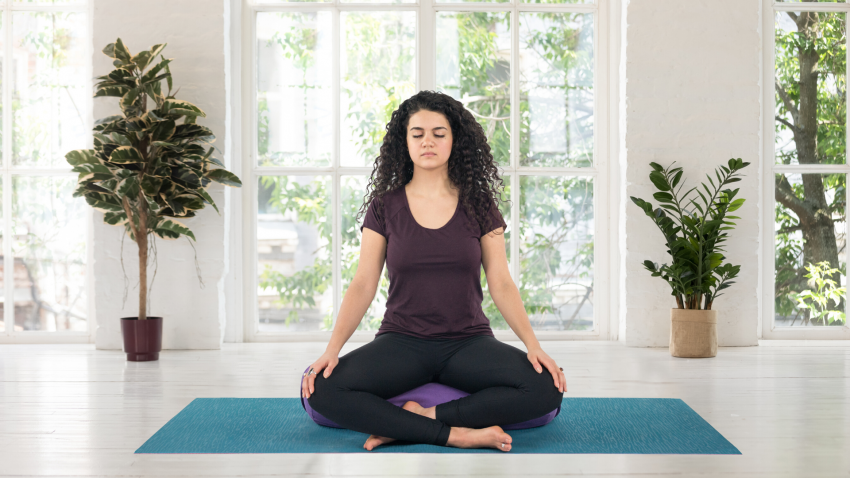 Woman practicing meditation for waking up and bedtime yoga