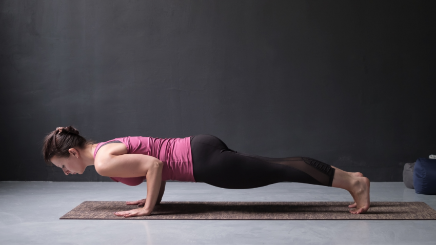 woman practicing four-limed staff yoga pose, chaturanga dandasana