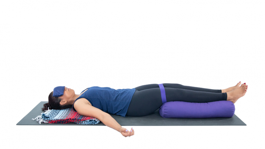 woman practicing restorative yoga svanasana modification with legs bound
