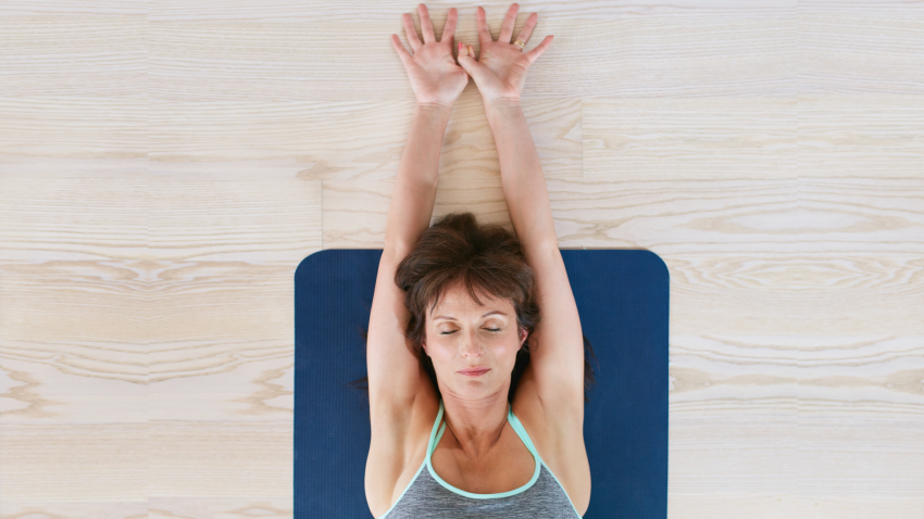 Woman stretching her arms overhead while lying on yoga mat.