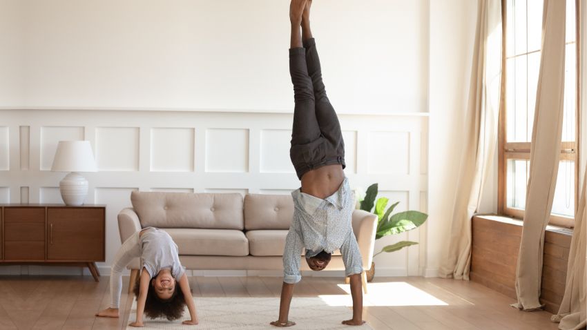 Father and child practicing yoga games together at home