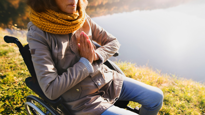 Woman in a wheelchair practicing meditation.