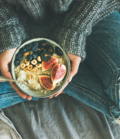 woman eating healthy plant-based diet with rice coconut porridge with figs, berries, hazelnut