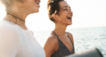 Woman smiling with her friend on the beach.
