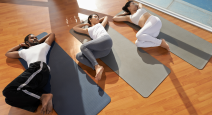 Group of yoga students practicing supine reclining yoga twist pose.